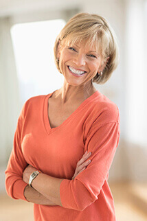 woman in coral sweater smiling